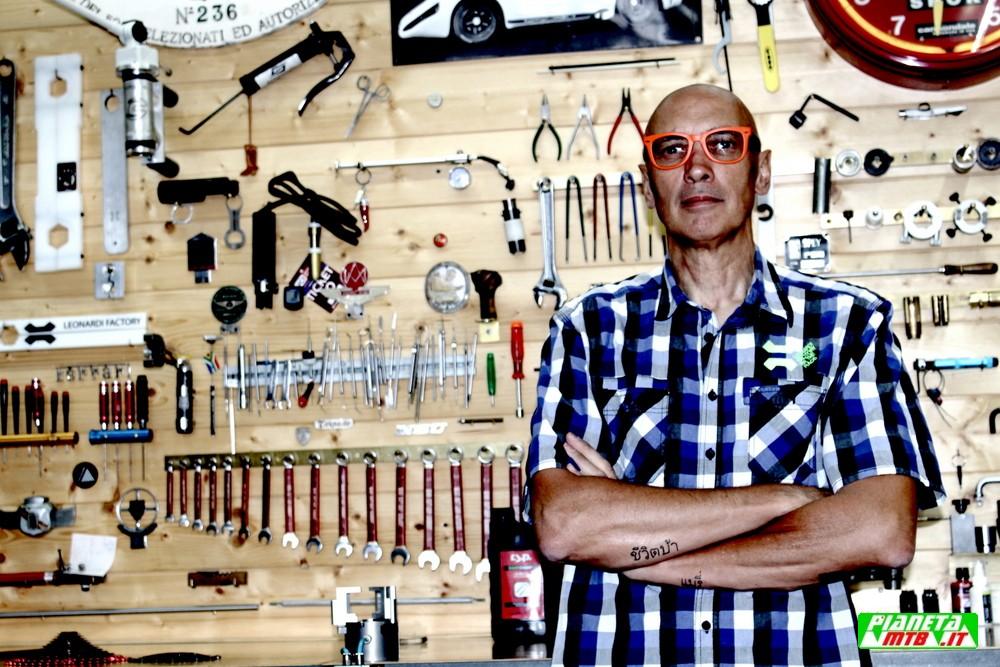 Michele Leonardi con occhiari arancio davanti al banco di lavoro
