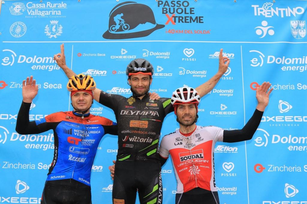 Elia Favilli sul podio della Passo Buole Xtreme con il vincitore Righettini e Dmitrii Medvedev